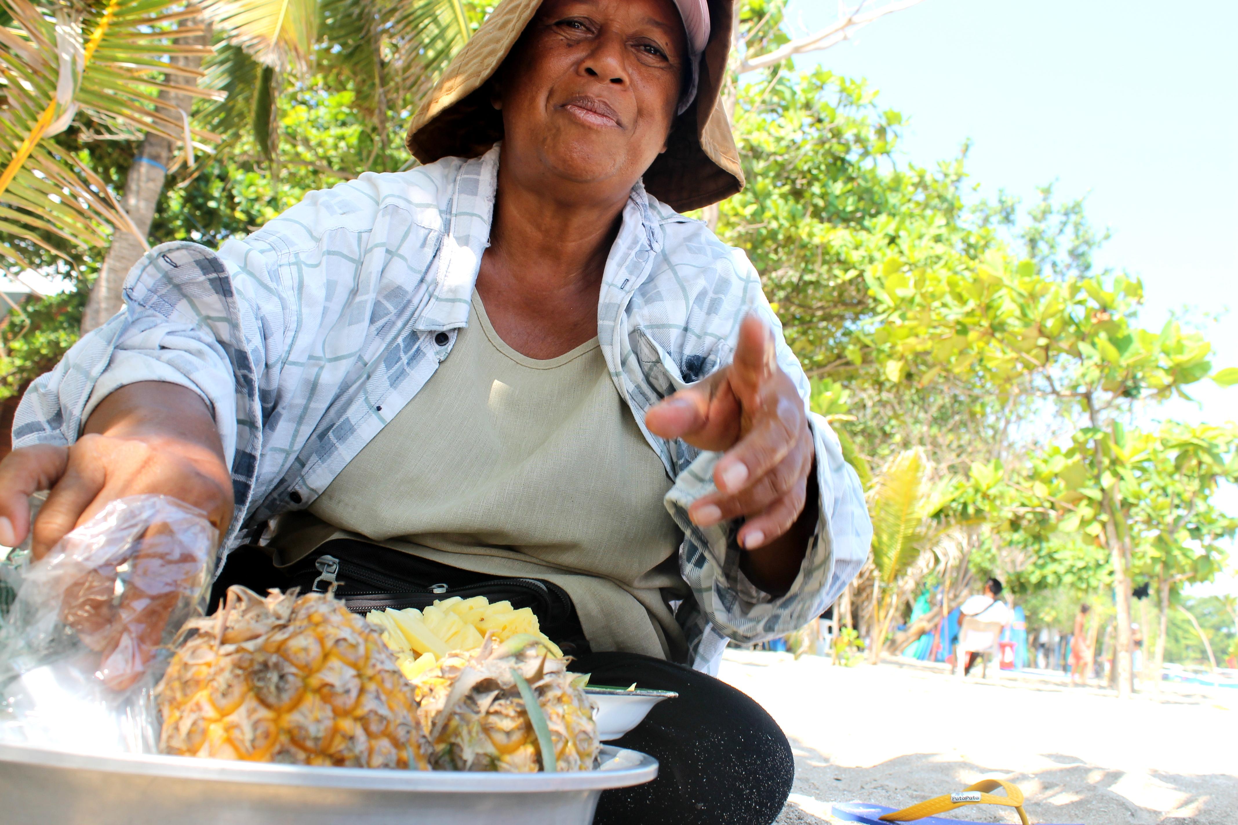 sprzedawczyni świeżych ananasów na plaży w Kucie